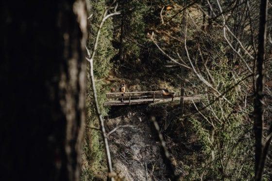 Mensch steht auf Brücke über Lücke des Pfades auf Etappe 8
